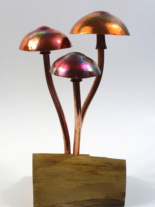 Three copper toadstools mounted on a log