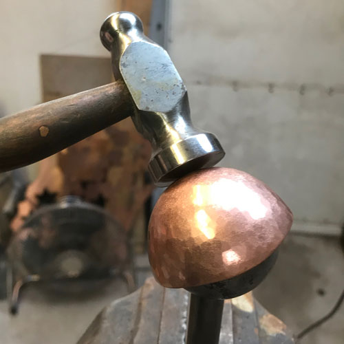 hand beating a copper spoon over a stake