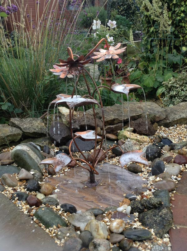 passion flower copper fountain set in a pebble pool